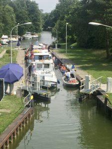Hausboote und Kajaks bei der Ausfahrt aus der Diemitzer Schleuse an der Mecklenbuger Seenplatte